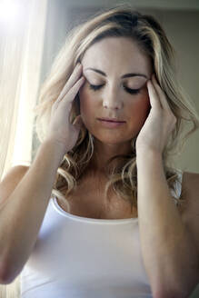 Young woman having headache at home - AJOF01042