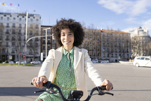 Afro young woman with electric bicycle in city - JCCMF01211