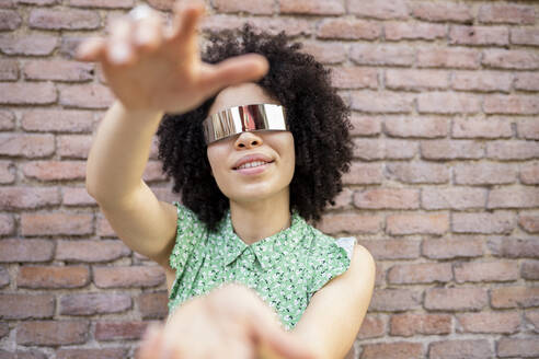 Young afro woman with futuristic sunglasses against brick wall - JCCMF01235