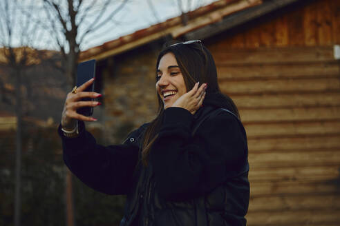 Happy young woman taking selfie through mobile phone by house - ACPF01142