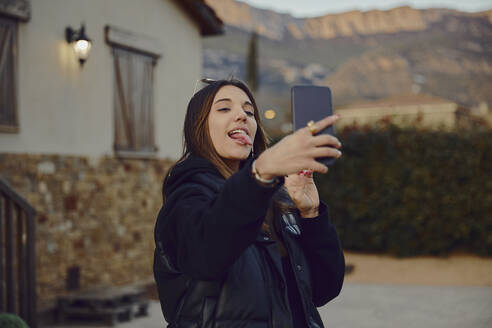 Playful woman sticking out tongue while taking selfie through mobile phone in front of house - ACPF01145