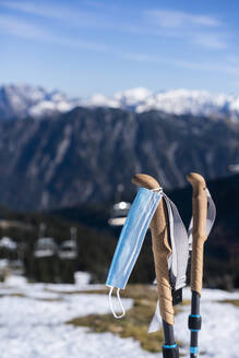 Protective face mask hanging on ski pole against mountains - AKLF00059