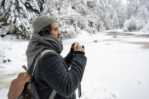 Young man with backpack and camera looking away while standing at forest - VPIF03560