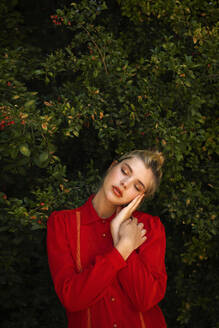 Young blond woman in red shirt standing against plants - TCEF01536