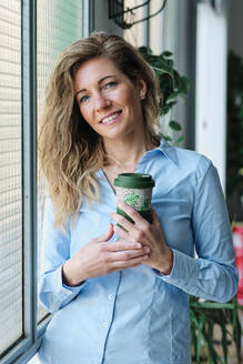 Mid adult woman with reusable cup standing by glass window - AGOF00051