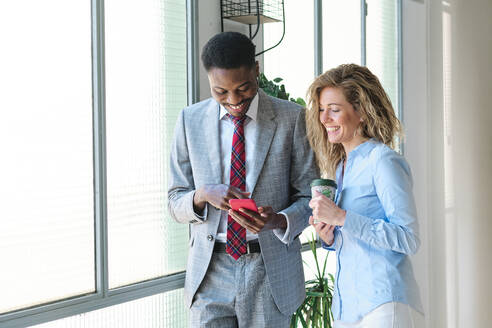 Male entrepreneur using smart phone while standing by smiling female colleague with coffee cup - AGOF00054
