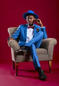 Confident man wearing blue suit sitting on chair against red background - AGOF00057