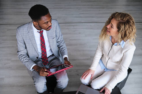 Male entrepreneur talking with female colleague holding digital tablet - AGOF00066