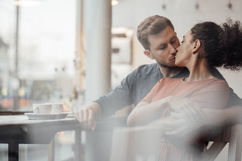 Young woman kissing man while sitting together at cafe - JOSEF03519