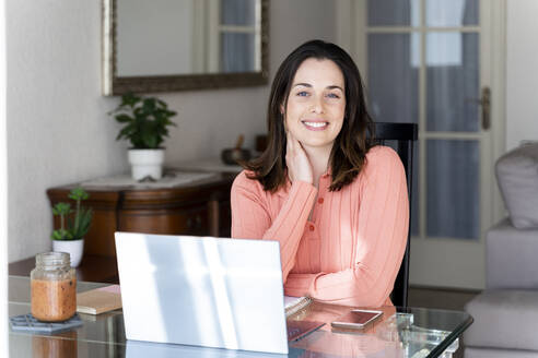 Beautiful smiling businesswoman with laptop sitting at dining table in home - AFVF08179