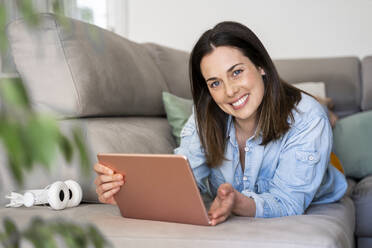 Beautiful woman smiling while holding digital tablet on sofa at home - AFVF08185