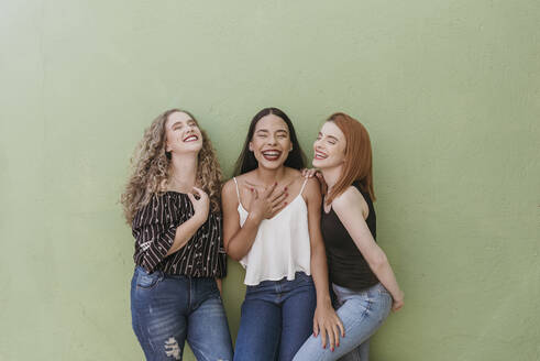 Carefree young women laughing while standing against green wall - DSIF00355