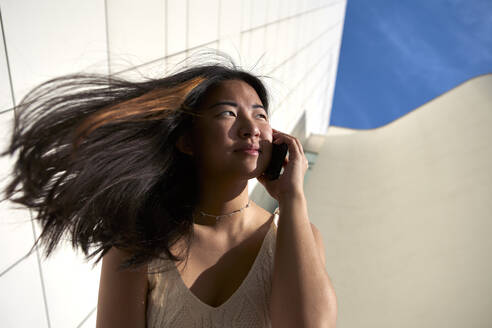 Beautiful woman looking away while talking on smart phone during sunny day - VEGF03934