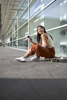 Young woman with smart phone sitting over skateboard on footpath - VEGF03952