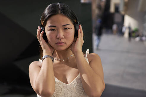 Young woman listening music through headphones outdoors - VEGF03955