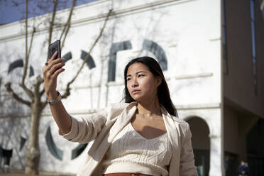 Stylish woman taking selfie through mobile phone on sunny day - VEGF03958