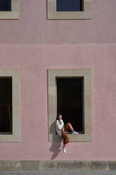 Asian woman sitting on window sill of building during sunny day - VEGF03961