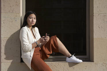 Confident woman with smart phone sitting on window sill - VEGF03967
