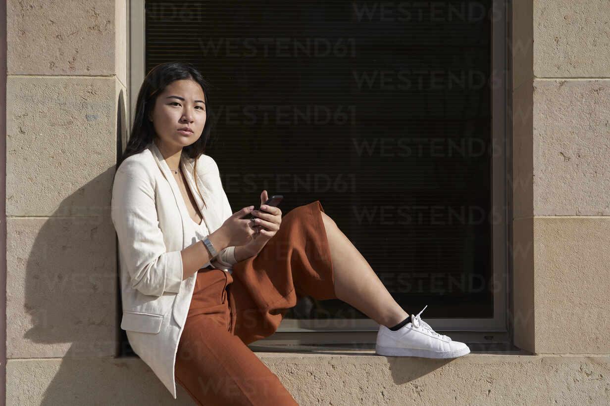 Selbstbewusste Frau mit Smartphone auf dem Fensterbrett sitzend - VEGF03967 - Veam/Westend61