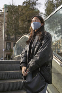 Asian woman with purse looking away while standing on escalator during pandemic - VEGF03970