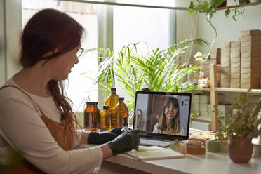 Female entrepreneur on video call with customer through laptop at workshop - VEGF03982