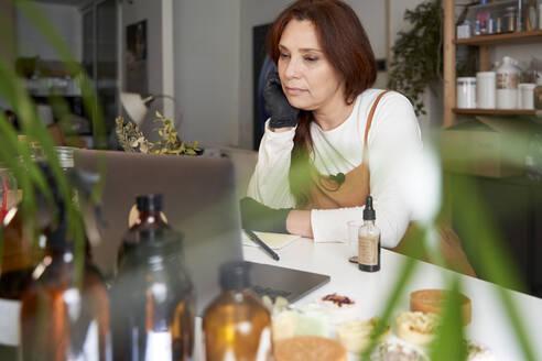 Female entrepreneur working on laptop at workshop - VEGF03985