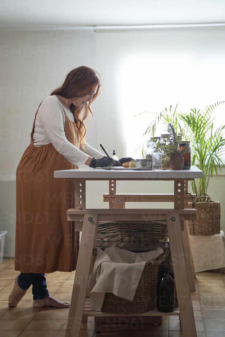 Reife Unternehmerin bei der Arbeit am Tisch in der Werkstatt - VEGF03988 - Veam/Westend61