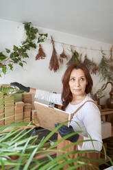 Female owner with clipboard holding products while standing in workshop - VEGF03994