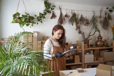 Female entrepreneur checking product on clipboard at workshop - VEGF03997