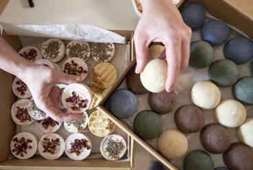 Female entrepreneur's hands holding handmade soaps over table - VEGF04000