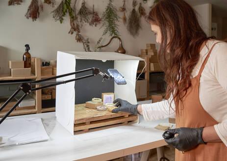 Female entrepreneur arranging handmade soaps in box at workshop - VEGF04003