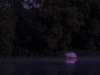 Lone motorboat floating in Saone river at purple night - HAMF00843