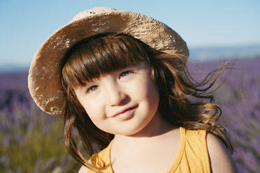 Portrait of cute little girl wearing straw hat standing outdoors - GEMF04696