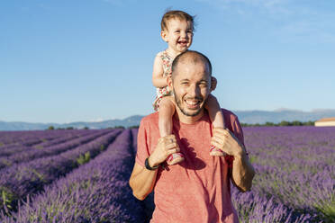 Portrait of father piggybacking baby daughter in vast summer lavender field - GEMF04705