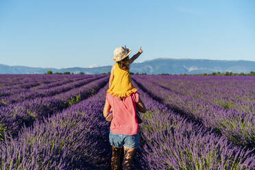 Little girl on shoulders of happy mother in a lavender field at afternoon in Valensole, Provence, France - GEMF04708