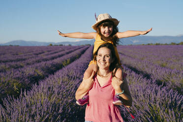 Portrait of mother piggybacking little daughter in vast summer lavender field - GEMF04711