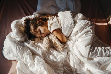 Sweet little girl sleeping in a motorhome with a stuffed rabbit at sunrise - GEMF04714
