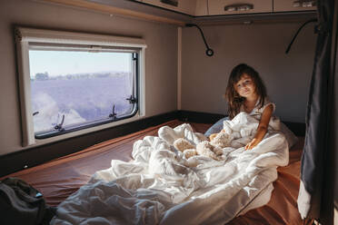 Sweet little girl sleeping in a motorhome with a stuffed rabbit at sunrise next lo lavender fields in Valensole, Provence, France - GEMF04717
