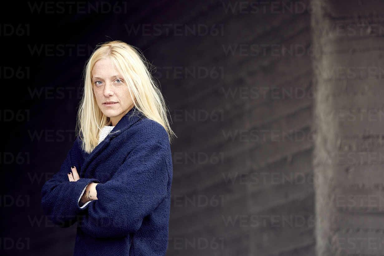 Junge Frau mit verschränkten Armen steht gegen die Wand im Parkhaus - UKOF00121 - Uta Konopka/Westend61
