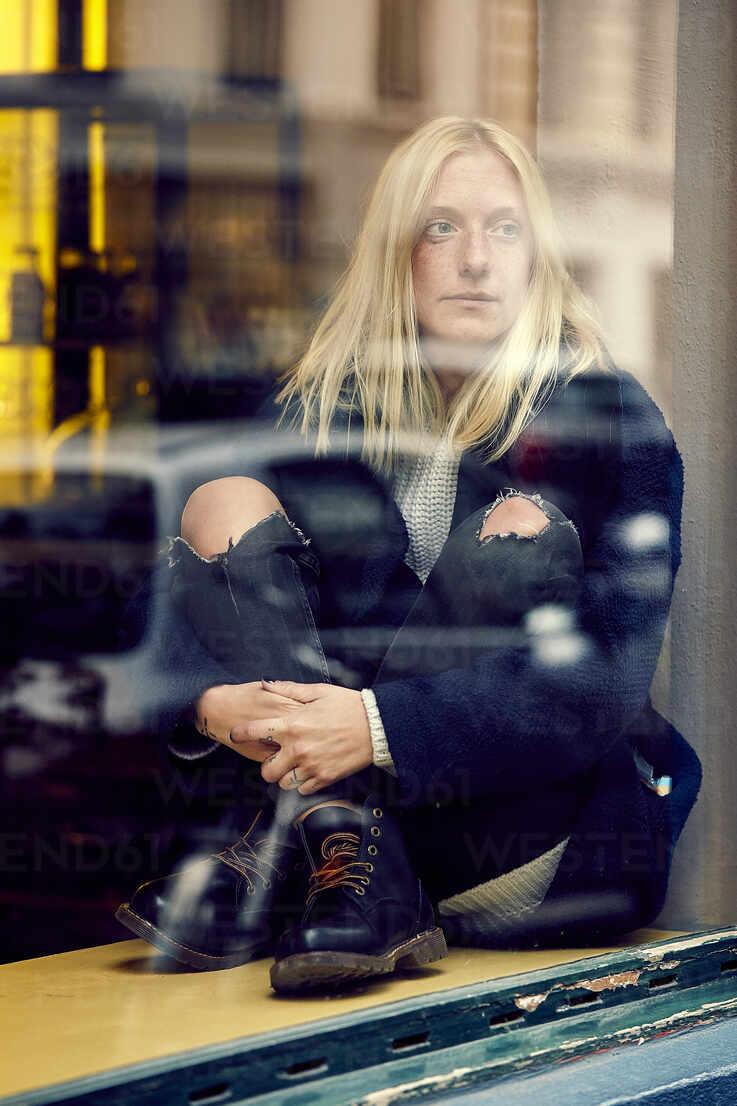 Junge blonde Frau sitzt am Fensterbrett - UKOF00130 - Uta Konopka/Westend61