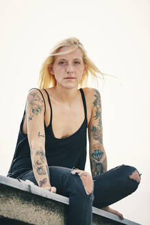 Tattooed young woman sitting on rooftop - UKOF00133