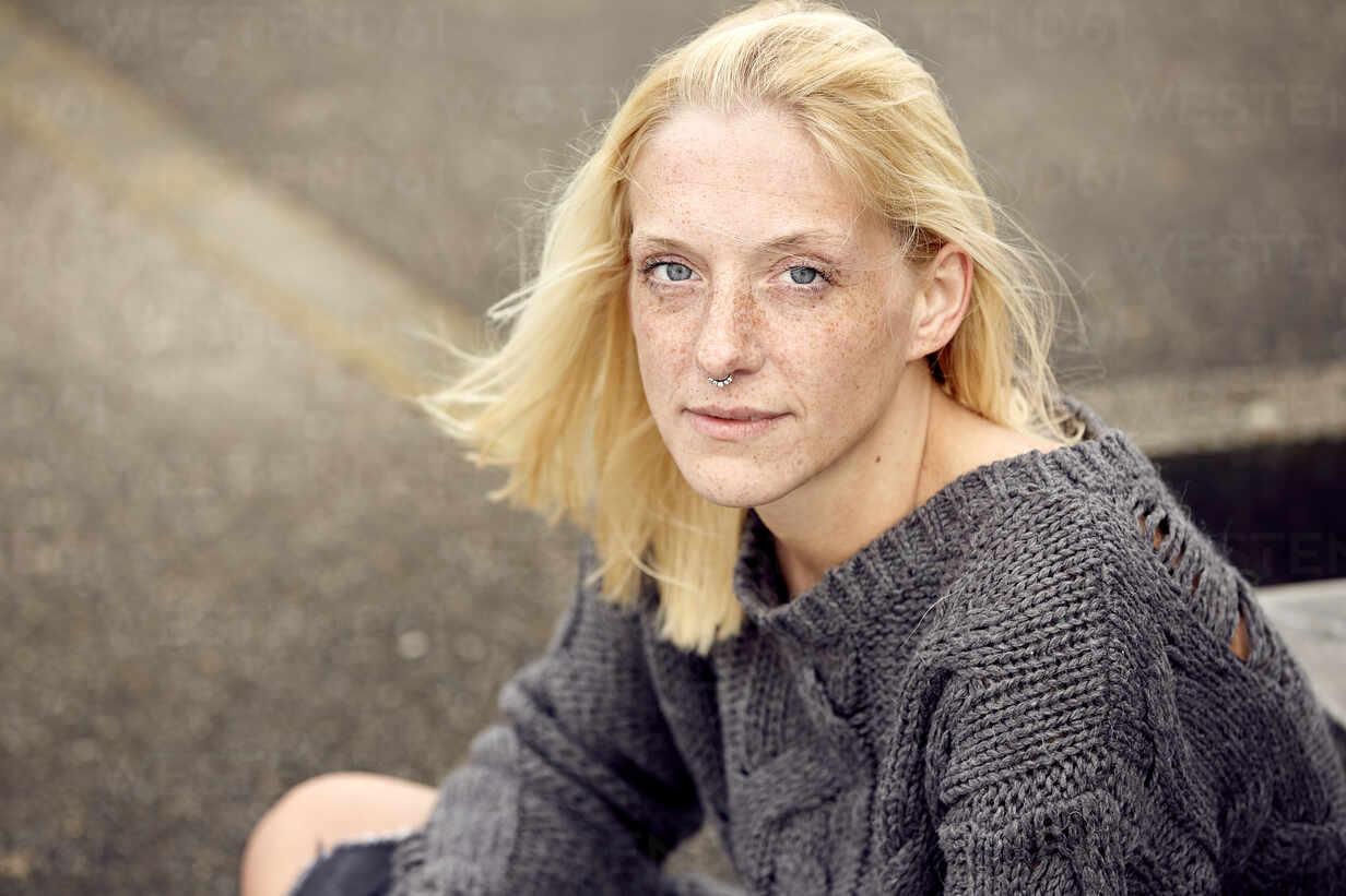 Blonde Frau mit Sommersprossen sitzt im Parkhaus - UKOF00142 - Uta Konopka/Westend61