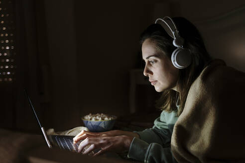 Woman with headphones and popcorn using laptop while lying at home - AFVF08207