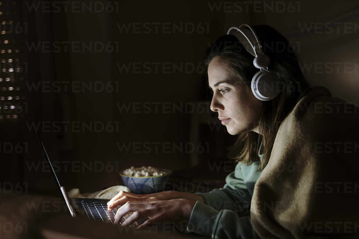 Woman with headphones and popcorn using laptop while lying at home - AFVF08207 - VITTA GALLERY/Westend61