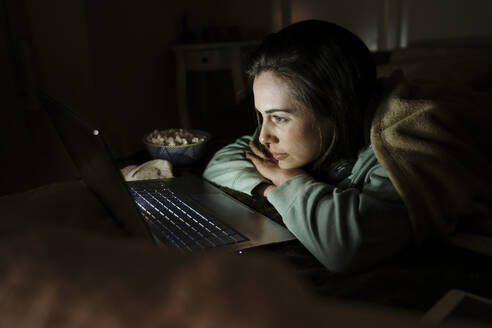Woman with popcorn watching movie on laptop in dark while relaxing at home - AFVF08210