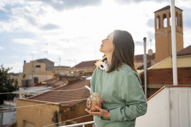 Young woman having fruit smoothie in the morning and waking up, stretching in balcony/terrace - AFVF08213