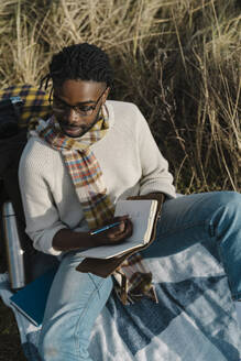 Man in eyeglasses holding diary sitting on blanket while looking away - BOYF01839