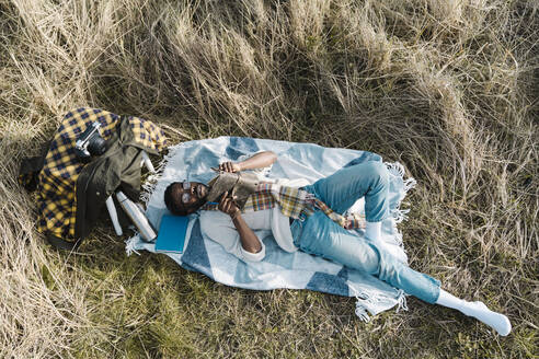 Relaxed man reading book while lying on blanket amidst dried plants - BOYF01842