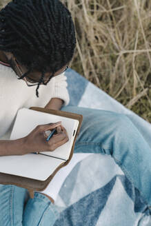 Young man writing on his diary while sitting at beach - BOYF01845