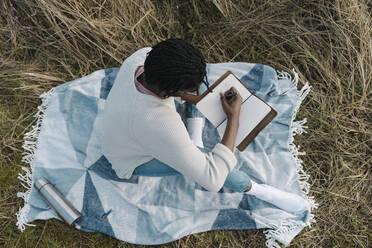 man on the beach writing on his journal. Dublin Ireland - BOYF01848